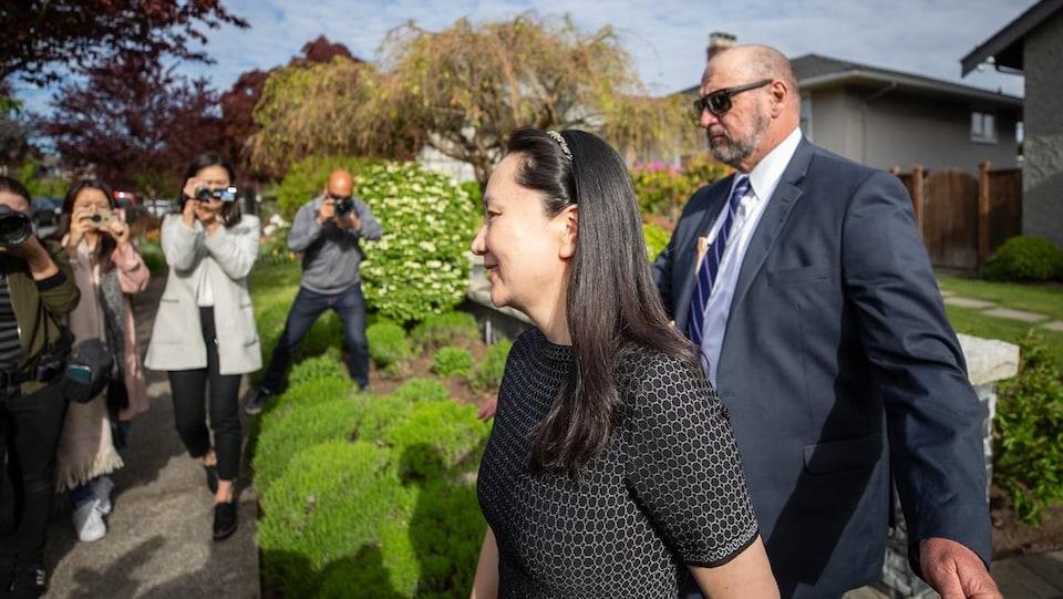 Une femme marche à côté d'un garde de sécurité pendant que des gens la photographient.