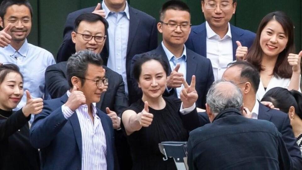 Plusieurs personnes montrent leur pouce en l'air, souriants, devant un photographe.