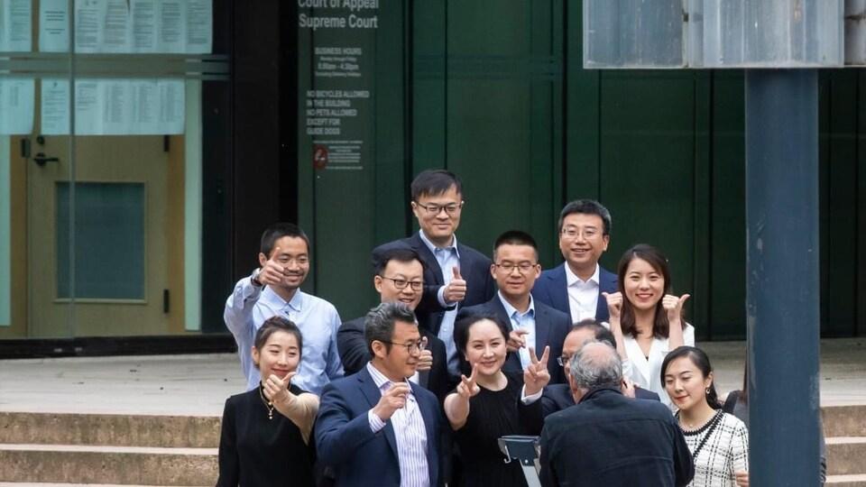 Meng Wanzhou, entourée de proches, fait le signe de la victoire devant le bâtiment de la Cour suprême de la Colombie-Britannique, samedi le 23 mai.