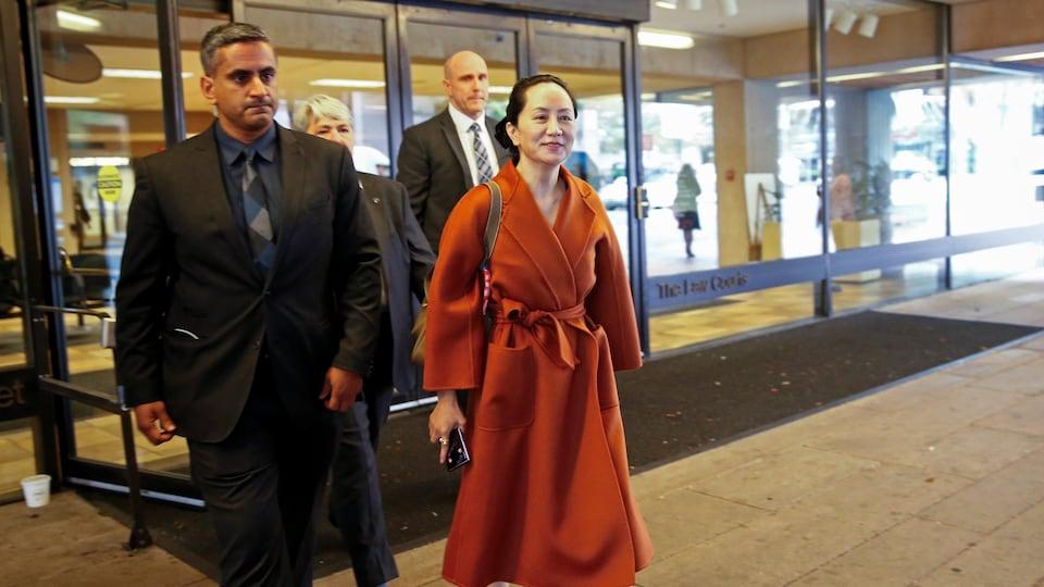 Escortée, Meng Wanzhou sourit à son arrivée à l'audience préliminaire. Elle porte à la cheville un bracelet électronique.