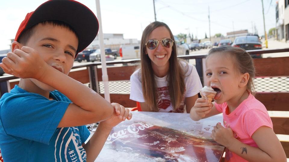 Une mère et deux enfants mangent une crème glacée.