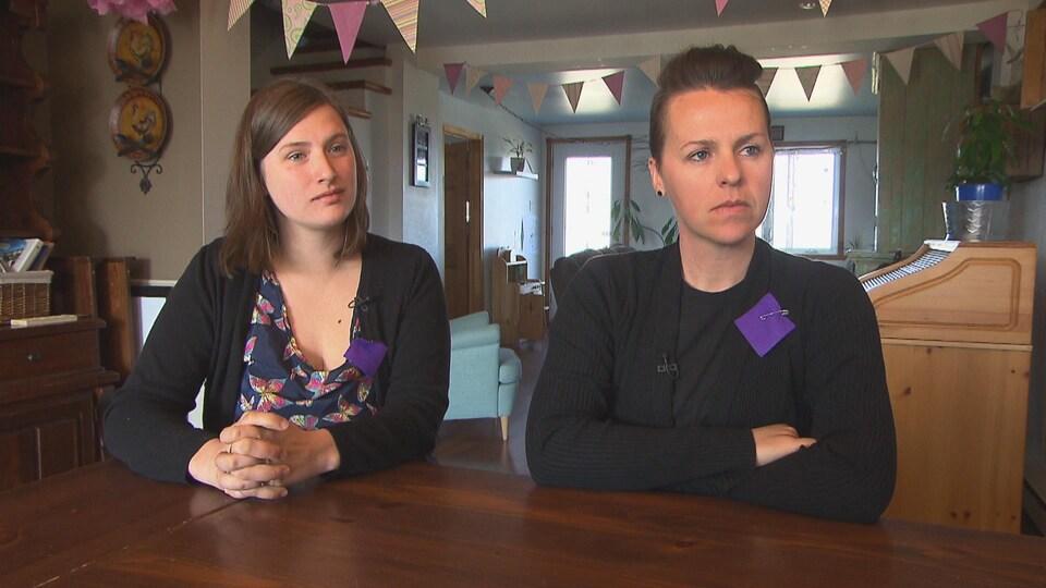 Les deux mamans assises à une table en entrevue avec un carré mauve sur leur chandail