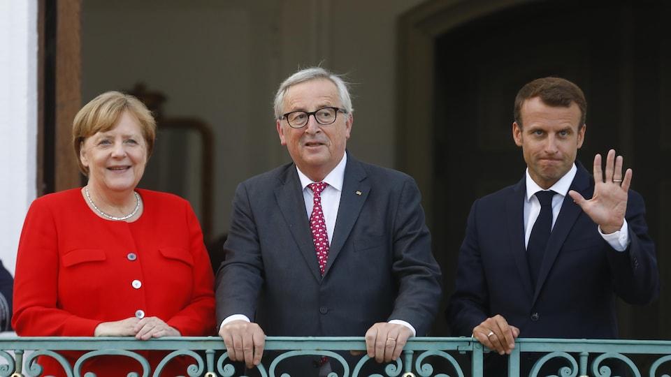 Angela Merkel, Jean-Claude Juncker et Emmanuel Macron saluent la foule depuis un balcon.