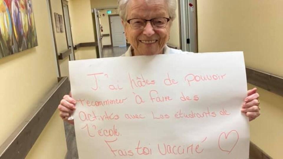 Edna St-Cyr tient une pancarte sur laquelle est écrit: J'ai hâte de pouvoir recommencer à faire des activités avec les étudiants de l'école, fais-toi vacciner.