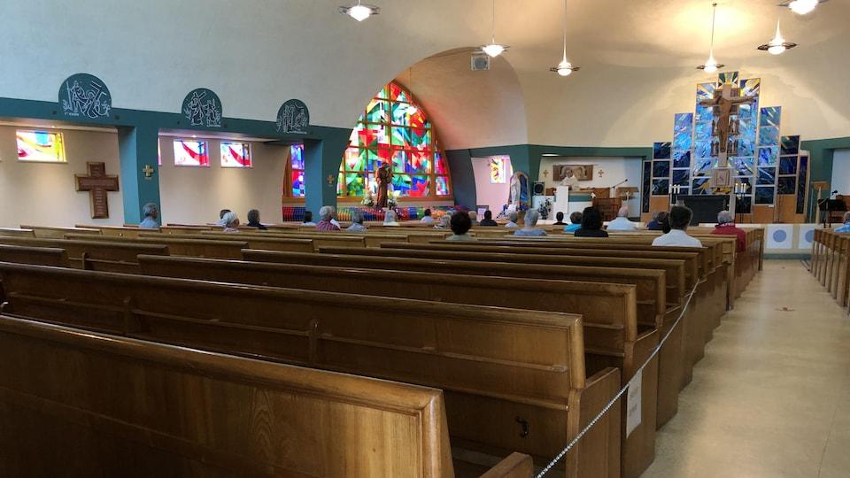 Des pèlerins sont assis dans des bancs et écoutent la messe.