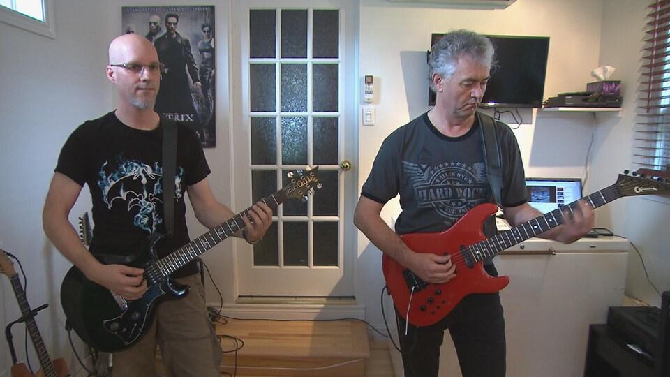 Bastien Deschênes et Jean Tremblay jouent de la guitare ensemble.
