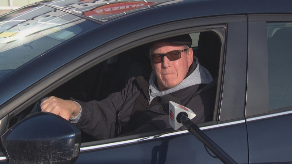 Un homme au volant de sa voiture stationnée. Une perche de micro est tendue vers lui.