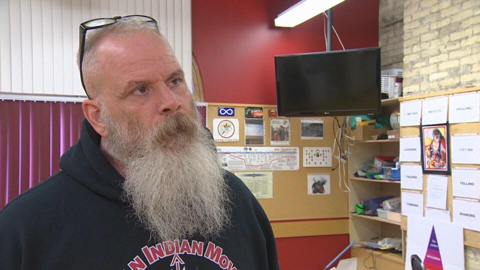 Un homme avec une barbe blanche debout dans un bureau.