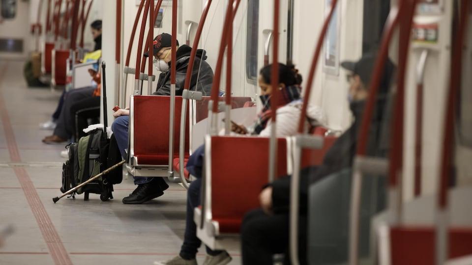 Plusieurs usagers sont assis à bonne distance les uns des autres dans une rame de métro. Certains portent des masques.