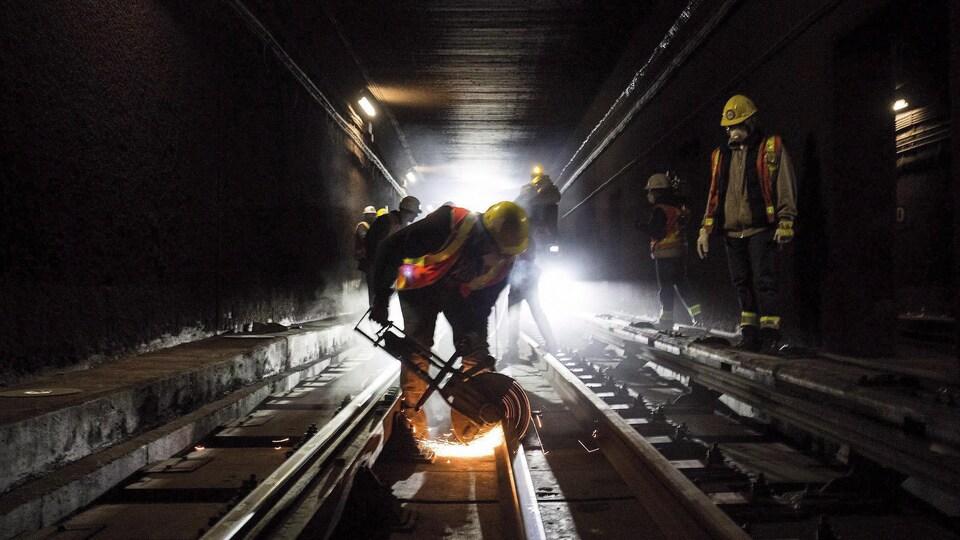 Un travailleur coupe un rail dans un tunnel du métro.