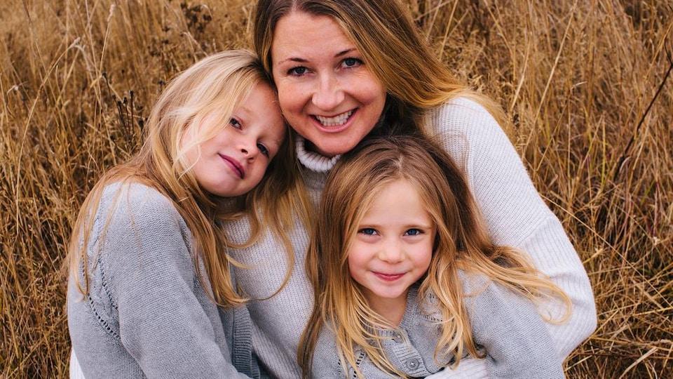 Photo avec une mère et deux jeunes filles souriantes avec des cheveux blonds.
