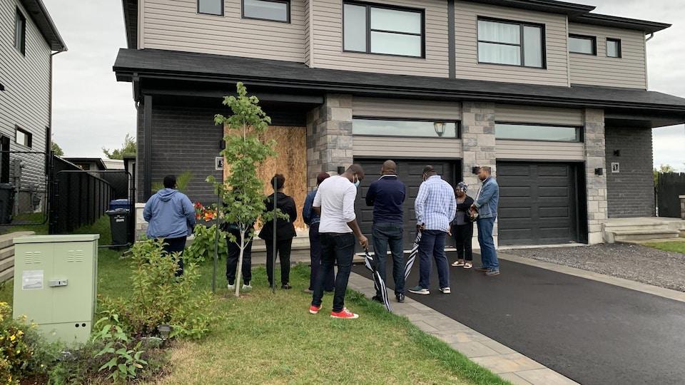 Des gens se recueillent devant une maison barricadée.