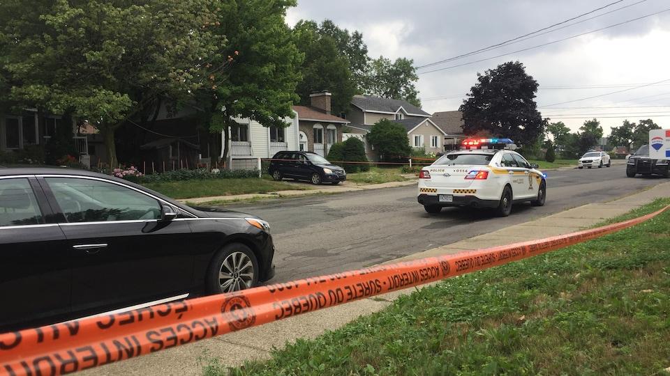 Une voiture patrouille de la SQ devant une maison qui est encerclée par des rubans où il est écrit : « Accès interdit ».