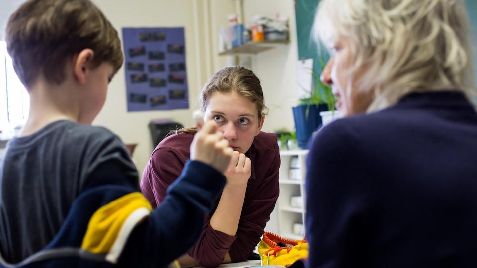 L'adolescente Lydia observe un jeune élève de maternelle dans une classe d'école.