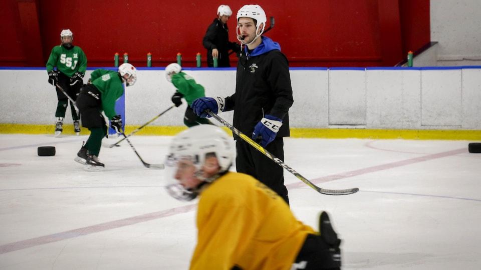 Un entraîneur de hockey sur la glace avec le sifflet dans la bouche et des joueurs en arrière-plan.