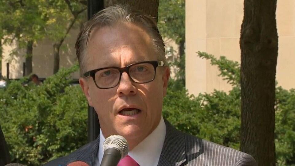 Un homme avec des lunettes et une cravate rose.