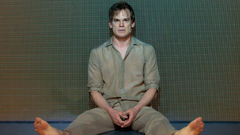 Michael C. Hall est assis sur scène.