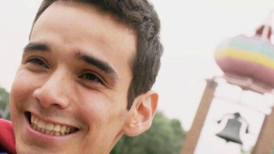 Un jeune homme souriant devant un clocher.