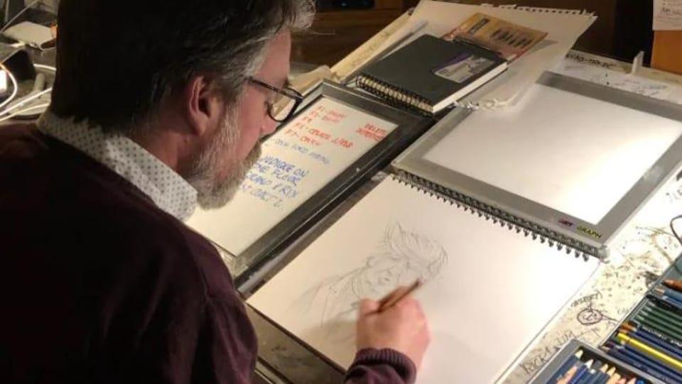 Le caricaturiste néo-brunswickois Michael de Adder au travail.