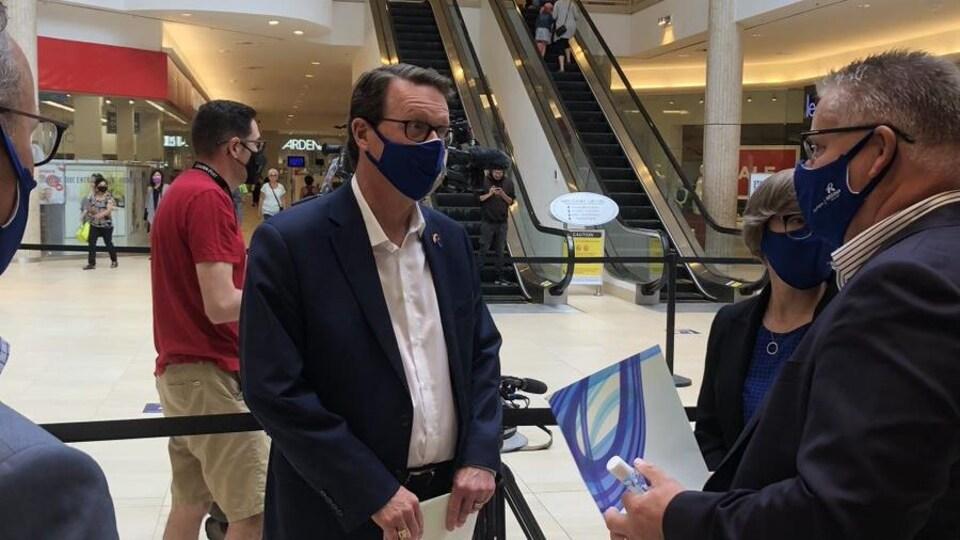 Le maire de Regina, portant un masque de protection, en train de bavarder.