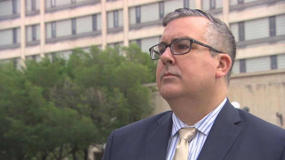 Un homme à lunettes, cheveux gris, en costume, devant l'hôtel de ville de Winnipeg une journée d'été.