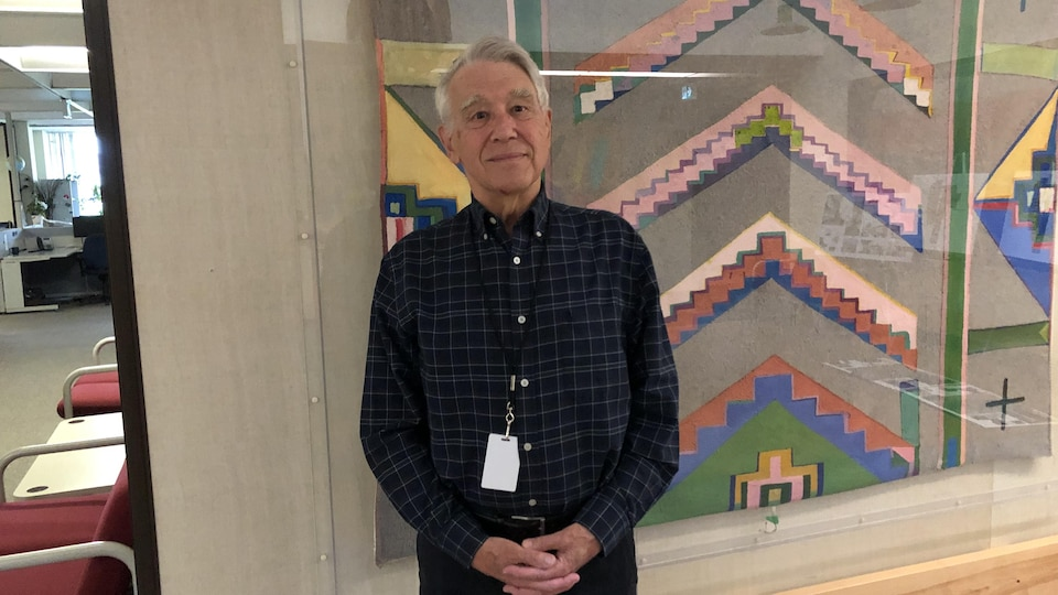 Un homme portant une chemise bleue et noire pose devant la caméra près du studio de radio de Radio-Canada à Regina.