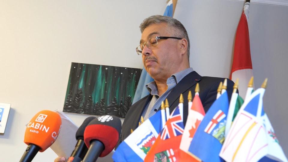 Un homme parle au micro derrière de petits drapeaux.