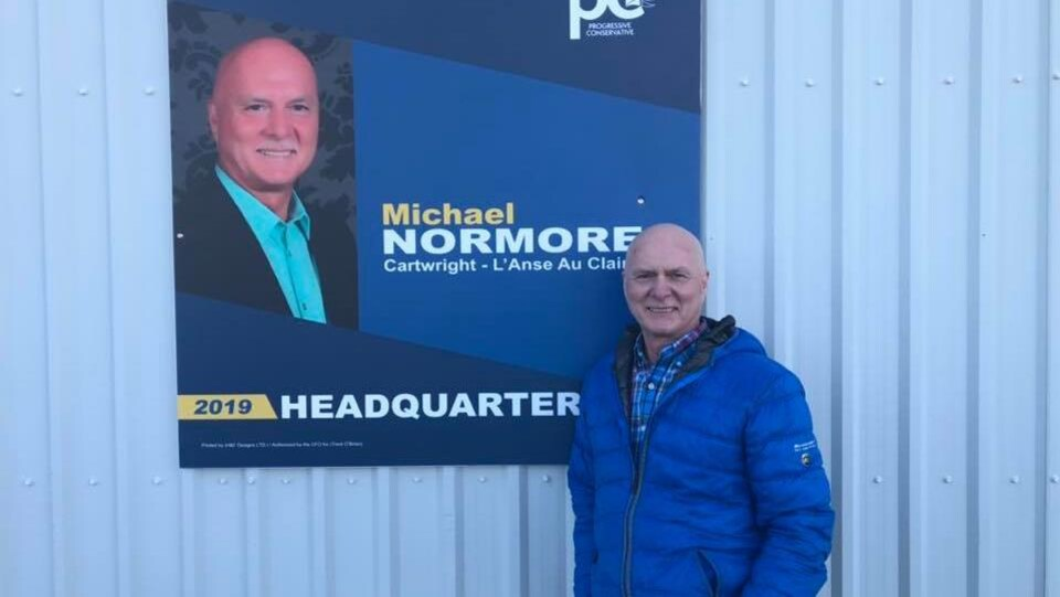 Michael Normore devant l'une de ses affiches électorales.