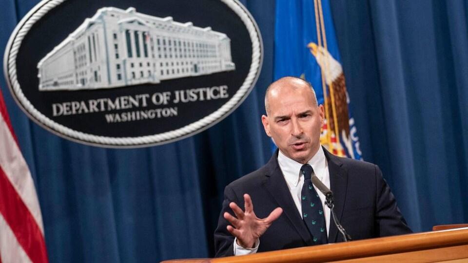 Michael Sherwin parle dans un micro devant un grand panneau où est inscrit : Département de la Justice, Washington.