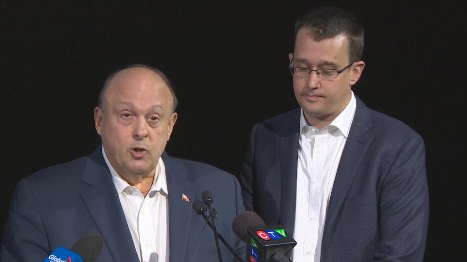 Photo de deux hommes en complet devant des micros.
