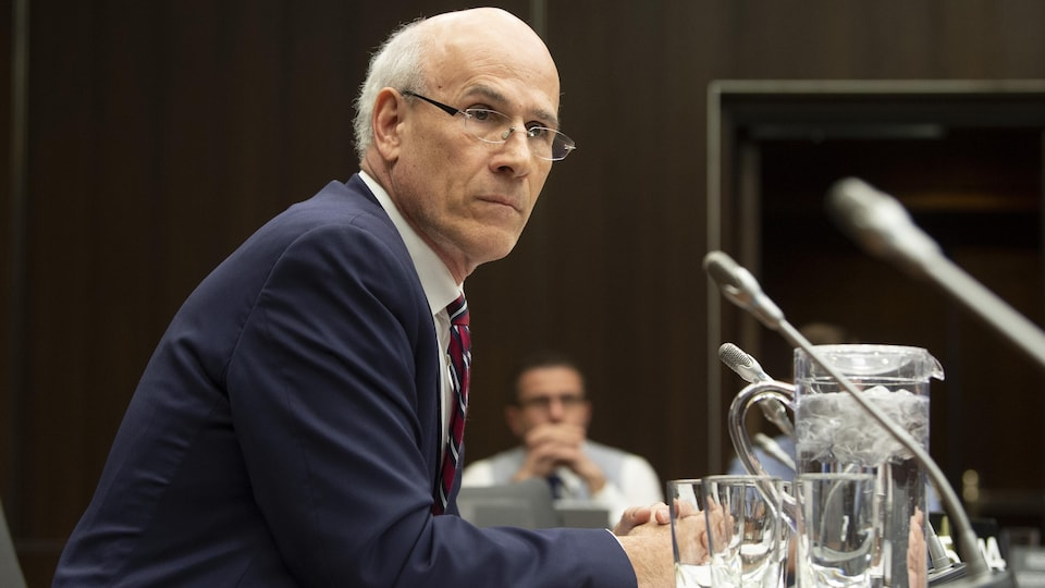 Michael Wernick, assis à une table, devant un micro.