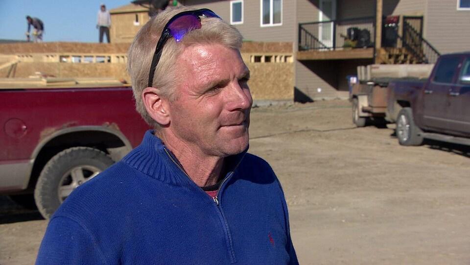 Micheal Groulx parle en entrevue devant une maison avec une remorque derrière.