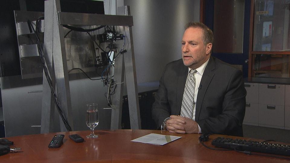 Michel Binette est assis à une table dans le cadre d'une entrevue.