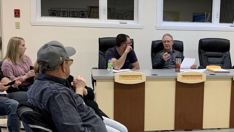 Deux hommes qui sont assis derrière une table et qui parlent et des citoyens qui écoutent.