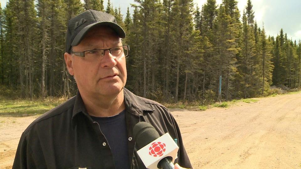 Un homme avec des lunettes devant un chemin forestier.