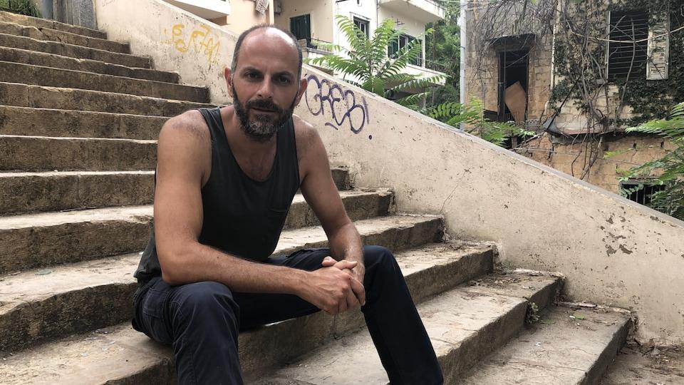 Un homme est assis dans les marches d'un édifice.