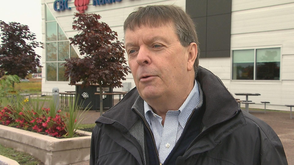 Michel Doucet à l'extérieur, devant l'édifice de Radio-Canada à Moncton.