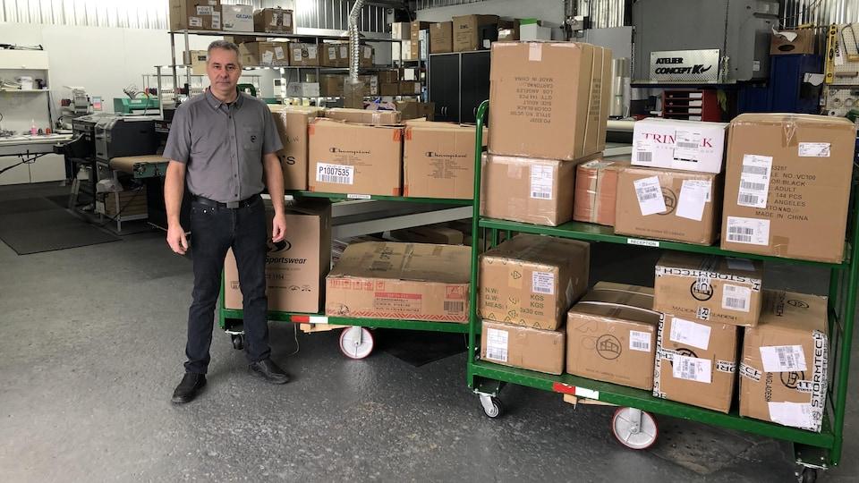 Michel Dugas, copropriétaire de Concept K, pose à côté de boîtes contenant des marchandises.