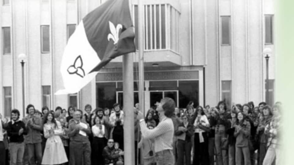 Photo noir et blanc de Michel Dupuis qu hisse le premier drapeau franco-ontarien.