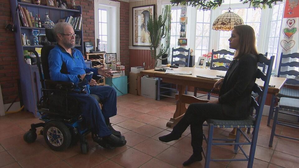 Michel Favreault dans son fauteuil roulant en entrevue avec la journaliste Marie-Ève Trudel