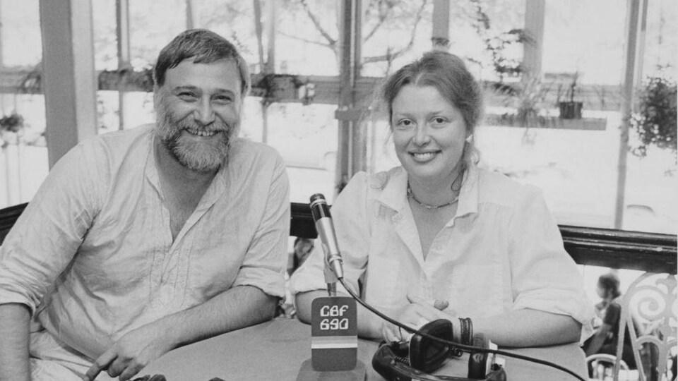L'homme et la femme sourient autour d'une table sur une terrasse.