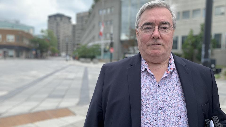 Michel Gauthier pose devant des immeubles, dehors.