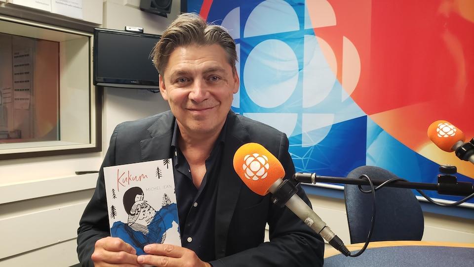 Michel Jean en studio tient son plus récent livre.