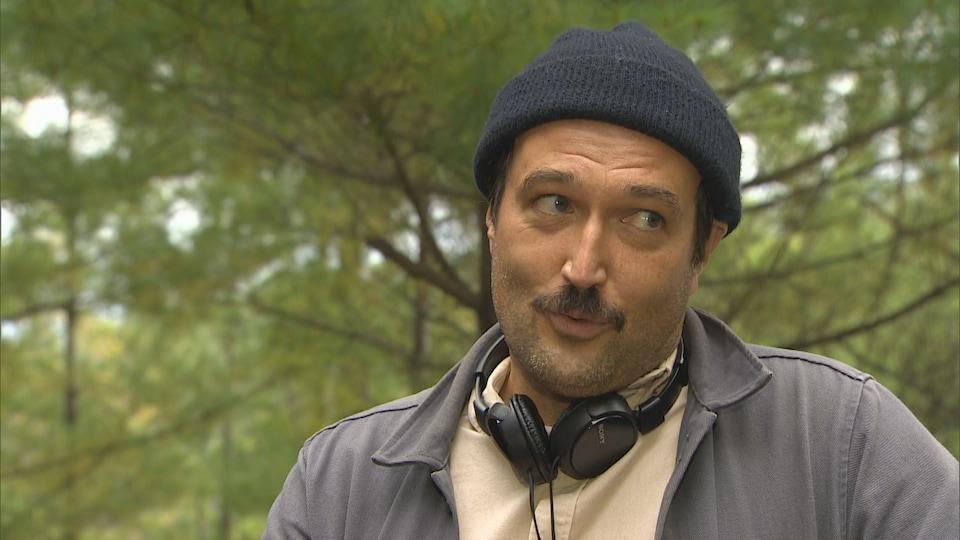 Michel Kandinsky lors d'une entrevue à l'extérieur devant une forêt.