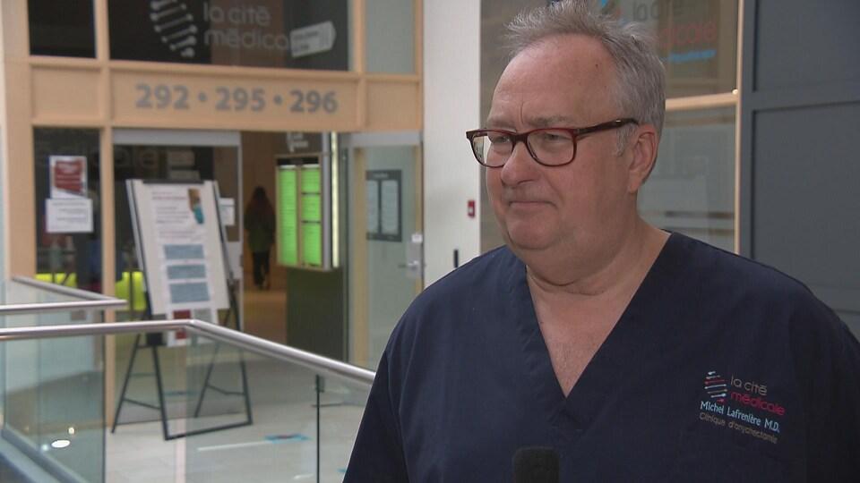 Le docteur devant l'entrée de sa clinique médicale.
