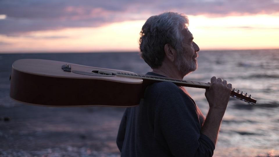 Michel Lalonde, sa guitare reposant sur son épaule.