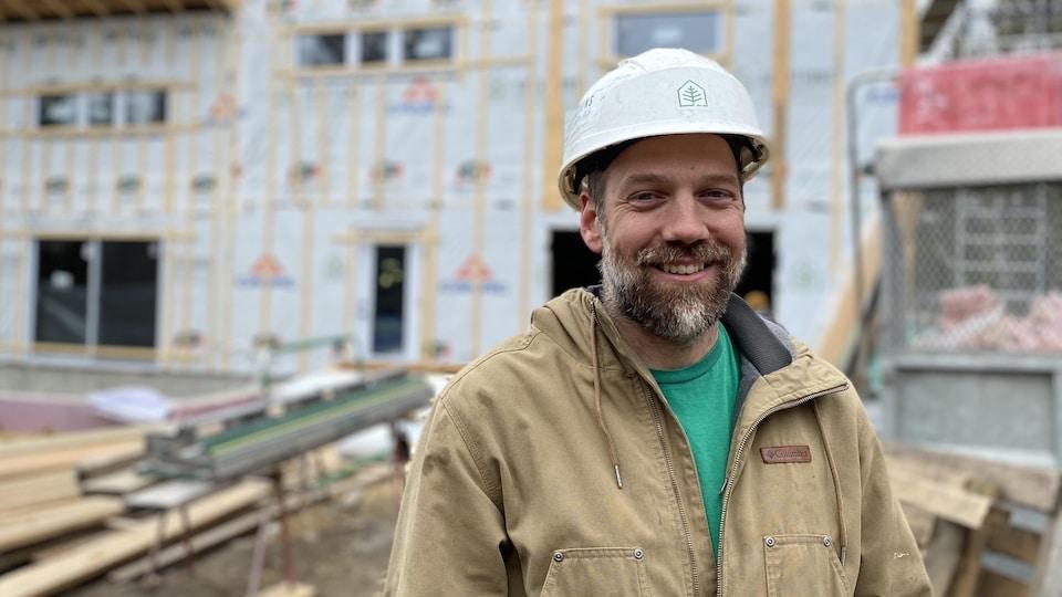Michel Leblanc devant un immeuble en construction.