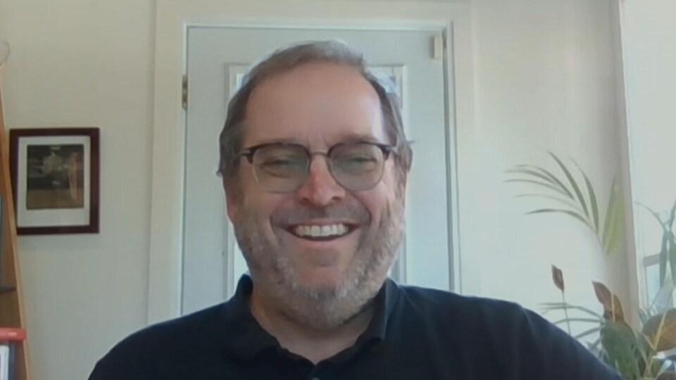 Un homme en train de rire pendant une entrevue par visioconférence.