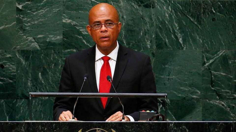 L'ancien président haïtien Michel Martelly se tient debout devant deux micros à la tribune de l'ONU.
