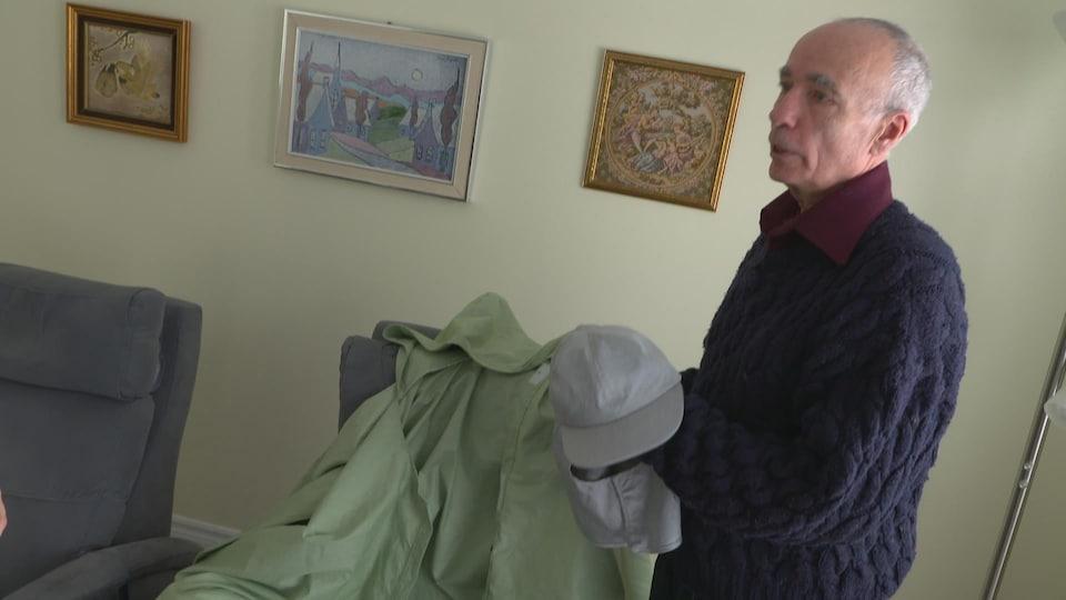 Un homme tient une casquette dans ses mains.
